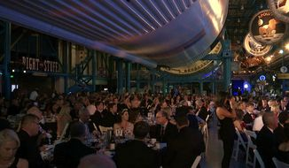 The black-tie Apollo Celebration Gala is held under a Saturn V rocket at the Kennedy Space Center in Cape Canaveral, Fla., on Saturday, July 21, 2018. The event kicked off a yearlong celebration of the upcoming 50-year anniversary of the first moon landing, and featured a panel discussion by astronauts, an awards ceremony and an auction of space memorabilia. (AP Photo/Alex Sanz)