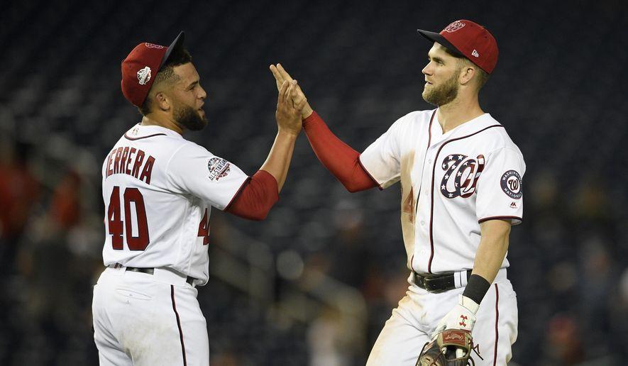 Washington Nationals' Kelvin Herrera (40) and Bryce Harper, right, celebrate after a baseball game against the Atlanta Braves, Sunday, July 22, 2018, in Washington. (AP Photo/Nick Wass) ** FILE **