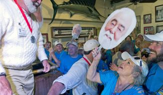 In this Saturday, July 21, 2018, photo provided by the Florida Keys News Bureau, Michael Groover, left, husband of celebrity chef Paula Deen, right, walks off the stage after competing in the semi-final round of the Hemingway Look-Alike Contest at Sloppy Joe's Bar in Key West, Fla. On his ninth attempt, Groover won the competition, the highlight event of the island city's annual Hemingway Days festival that ends Sunday, July 22. (Andy Newman/Florida Keys News Bureau via AP)