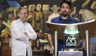 Hamilton playwright Lin-Manuel Miranda gives a press conference at the Art Museum of Puerto Rico, as his father Luis Miranda looks on, in San Juan, Puerto Rico, Sunday, July 22, 2018. Miranda announced he has helped create a multimillion-dollar fund to boost the arts in the U.S. territory as it struggles to recover from Hurricane Maria. (AP Photo/Carlos Giusti)