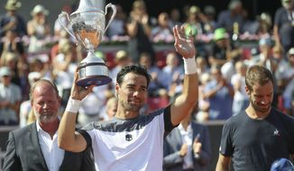 Italy's Fabio Fognini celebrates holding the trophy after defeating France's Richard Gasquet 6-3, 3-6, 6-1 in the final of the Swedish Open tennis tournament, in Bastad, Sweden, Sunday July 22, 2018. (Adam Ihse/TT via AP)