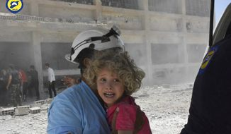 FILE - In this Wednesday, June 14, 2017, file photo, provided by the Syrian Civil Defense group known as the White Helmets, shows a civil defense worker carrying a child after airstrikes hit a school housing a number of displaced people in the western part of the southern Daraa province of Syria. The Israeli military said Sunday it had rescued members of a Syrian volunteer civil organization, known as White Helmets, from the volatile frontier area and evacuated them to a third country, the first such Israeli intervention in Syria's lengthy civil war. (Syrian Civil Defense White Helmets via AP, File)