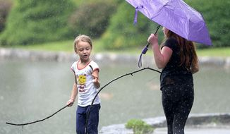 Summer Barnard, left, 5 and sister Alexis Barbard 9 of Hagerstown, Md., play at Hagerstown City Park during intermittent rain showers Monday, July 23, 2018. (Colleen McGrath /The Herald-Mail via AP)