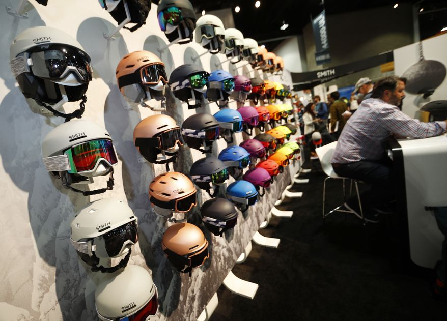 Ski helmets line a wall in the Smith booth at the Outdoor Retailer and Snow Show in the Colorado Convention Center Friday, Jan. 26, 2018, in Denver. Sales of outdoor equipment are slipping as millennials drive changes in U.S. consumer habits by favoring clothes and sporting goods that are less specialized and more versatile, analysts say.  (AP Photo/David Zalubowski)
