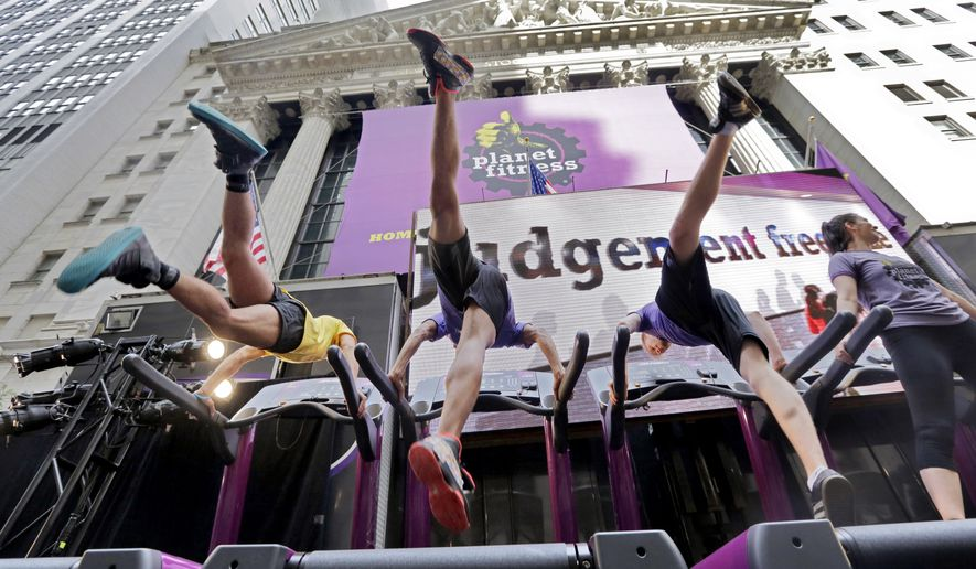 Planet Fitness dancers perform on treadmills outside the New York Stock Exchange after the company's IPO, Thursday, Aug. 6, 2015. (AP Photo/Richard Drew) ** FILE **