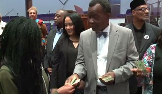 Democratic Party candidate for Chicago mayor Willie Wilson hands out cash to potential voters at New Covenant Missionary Baptist church, July 22, 2018. (Image: WGN-TV Chicago)