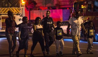 Police escort civilians away from the scene of a shooting, Sunday, July 22, 2018, in Toronto. (Frank Gunn/The Canadian Press via AP)