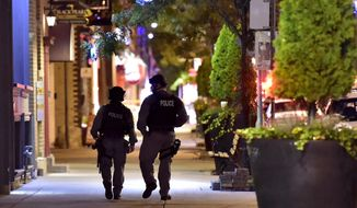Tactical police officers walk along Danforth Avenue at the scene of a shooting in Toronto on Monday, July 23, 2018. (Frank Gunn/The Canadian Press via AP)