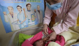 """In this April 25, 2017, photo, a baby receives a vaccine shot next to a poster which reads """"Standardize vaccination and build a healthy China"""" at a hospital in Handan in north China's Hebei province. China's No. 2 leader has ordered an investigation of its vaccine industry after violations by a rabies vaccine producer prompted a public outcry following scandals over shoddy drugs and food. (Chinatopix via AP)"""