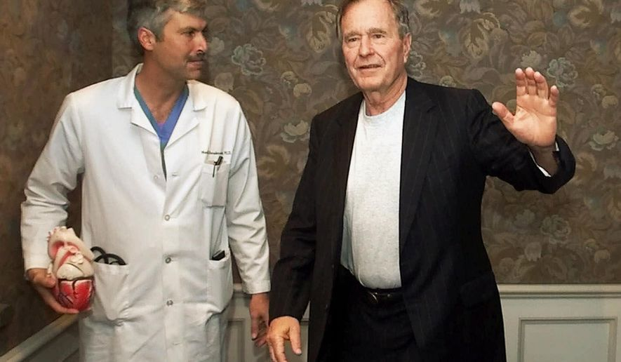 Former President George H.W. Bush waves as he leaves Methodist Hospital with his cardiologist, Mark Hausknecht, after a news conference in Houston. Hausknecht, who once treated former President George H.W. Bush, was fatally shot by a fellow bicyclist Friday, July 20, 2018, while riding through a Houston medical complex, and police were trying to determine if the shooting was random or a targeted act. (AP Photo/David J. Phillip, File)