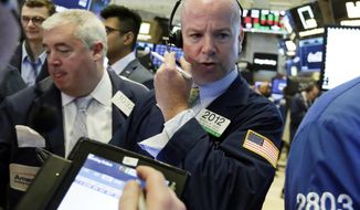 Trader Patrick Casey, center, works on the floor of the New York Stock Exchange, Monday, July 23, 2018. Stocks are opening slightly lower on Wall Street, led by declines in technology companies and retailers. (AP Photo/Richard Drew)