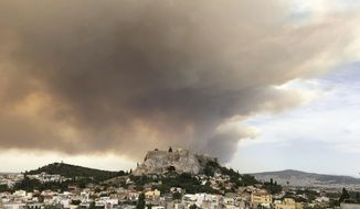 A pall of smoke turns large parts of the sky orange, with the ancient Acropolis hill at centre, as a forest fire burns in a mountainous area west of Athens, sending nearby residents fleeing, Monday, July 23, 2018. The fire department said five water-dropping planes and two helicopters were battling the blaze Monday in the Geraneia mountains near the seaside settlement of Kineta between Athens and Corinth, along with 30 firetrucks and 70 firefighters. (AP Photo/Theodora Tongas)
