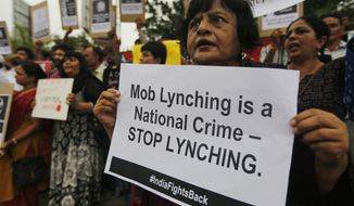Indians hold placards and shout slogans during a protest against mob attacks in Ahmadabad, India, Monday, July 23, 2018. A woman was lynched in central India on rumors that she was part of a gang that kidnapped children, police said Monday, days after the country's highest court called for immediate steps to control deadly mob violence across the country. (AP Photo/Ajit Solanki)