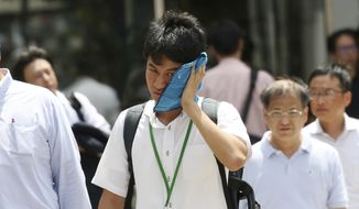 A man wipes the sweat from his face in the scorching heat at a business district in Tokyo, Monday, July 23, 2018. Searing hot temperatures are forecast for wide swaths of Japan and South Korea in a long-running heat wave. The mercury is expected to reach 39 degrees Celsius (102 degrees Fahrenheit) on Monday in the city of Nagoya in central Japan and reach 37 in Tokyo. Deaths have been reported almost every day. (AP Photo/Koji Sasahara)