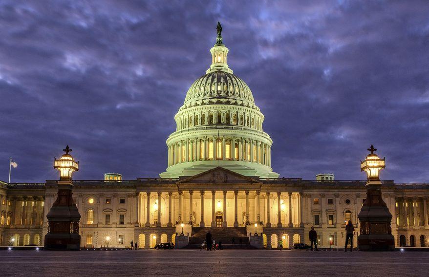 In this Jan. 21, 2018, file photo, lights shine inside the U.S. Capitol Building as night falls in Washington. (AP Photo/J. David Ake) ** FILE **