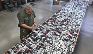 FILE - In this April 10, 2009, file photo, Correctional Officer Jose Sandoval inspects one of the more than 2,000 cell phones confiscated from inmates at California State Prison, Solano in Vacaville, Calif. Judges in California and South Carolina have ordered cellphone carriers to shut down nearly 200 contraband phones used by inmates in state prisons to coordinate drug deals, gang operations and even murders. California's corrections chief tells The Associated Press on Monday, July 23, 2018, that it's the first time prison officials obtained warrants requiring a mass shutdown of contraband phones. (AP Photo/Rich Pedroncelli, File)