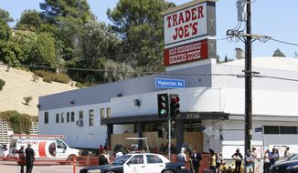 Police officers guard the entrance to the Trader Joe's Los Feliz store, as it remains closed for business, Sunday, July 22, 2018, in Los Angeles. A day earlier, Trader Joe's employee Melyda Corado was shot and killed at the store by a suspect being chased by police. (AP Photo/Damian Dovarganes)