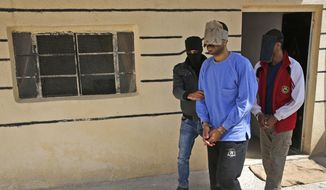 """In this file photo dated Friday, March 30, 2018, a Kurdish security officer escorts Alexanda Kotey, left, and El Shafee Elsheikh, who were allegedly among four British jihadis who made up a brutal Islamic State cell dubbed """"The Beatles,"""" at a security center in Kobani, Syria. (AP Photo/Hussein Malla, FILE)"""