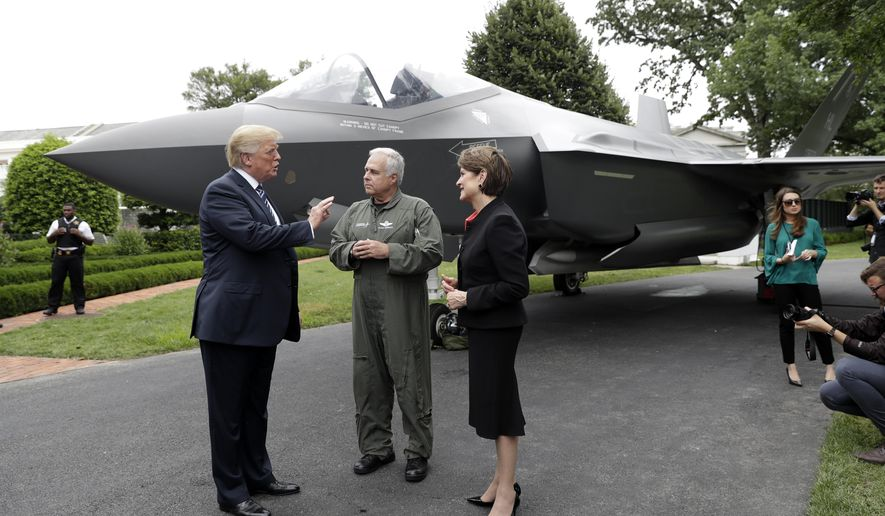 """In this July 23, 2018, file photo, President Donald Trump talks with Lockheed Martin president and CEO Marilyn Hewson and director and chief test pilot Alan Norman in front of a F-35 as he participates in a """"Made in America Product Showcase"""" at the White House in Washington. On Oct. 28, 2019, the Pentagon and Lockheed Martin on completed a $34 billion deal that will result in the delivery of 478 F-35 Lightning II fighter jets. (AP Photo/Evan Vucci) **FILE**"""