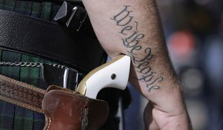 In this Jan. 26, 2015 file photo, a supporter of open carry gun laws, wears a pistol as he prepares for a rally in support of open carry gun laws at the Capitol, in Austin, Texas. (AP Photo/Eric Gay, File)