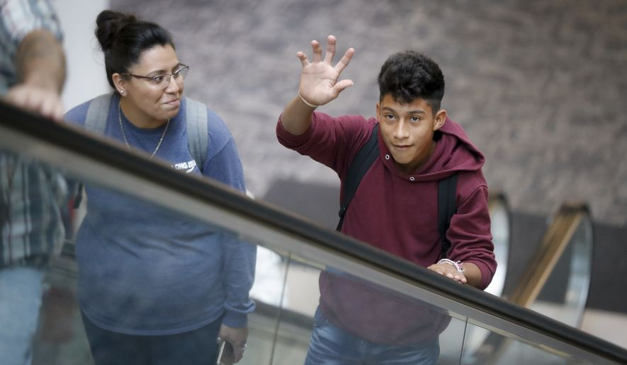 """Samuel Cazun, of Guatemala, right, waves to his family at Cincinnati/Northern Kentucky International Airport before reuniting with his father Edvin after being separated about a month ago at the southern border after they crossed the Rio Grande into the United States, Monday, July 23, 2018, in Hebron, Ky. Edvin said they were separated at the """"detention"""" and he spent 15 days without knowing anything about his son. (AP Photo/John Minchillo)"""
