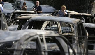 People stand amid the charred remains of burned-out cars in Mati east of Athens, Tuesday, July 24, 2018. Twin wildfires raging through popular seaside areas near the Greek capital have torched homes, cars and forests and killed at least 49 people, authorities said Tuesday, raising the death toll after rescue crews reported finding the bodies of more than 20 people huddled together near a beach. (AP Photo/Thanassis Stavrakis)