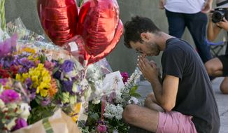 ADDS TO CLARIFY CORADO WAS SHOT TO DEATH IN A GUNFIGHT BETWEEN A GUNMAN AND POLICE - Paolo Singer, 27, a Silver Lake resident, prays at a makeshift memorial of flowers, candles and notes growing on the sidewalk outside the Silver Lake Trader Joe's store in Los Angeles, Monday, July 23, 2018. Two days earlier, Trader Joe's employee Melyda Corado was shot and killed at the store in a gunfight between a gunman and police. Grieving family members, co-workers and customers on Sunday remembered Corado as lively, hardworking and always smiling. (AP Photo/Damian Dovarganes)