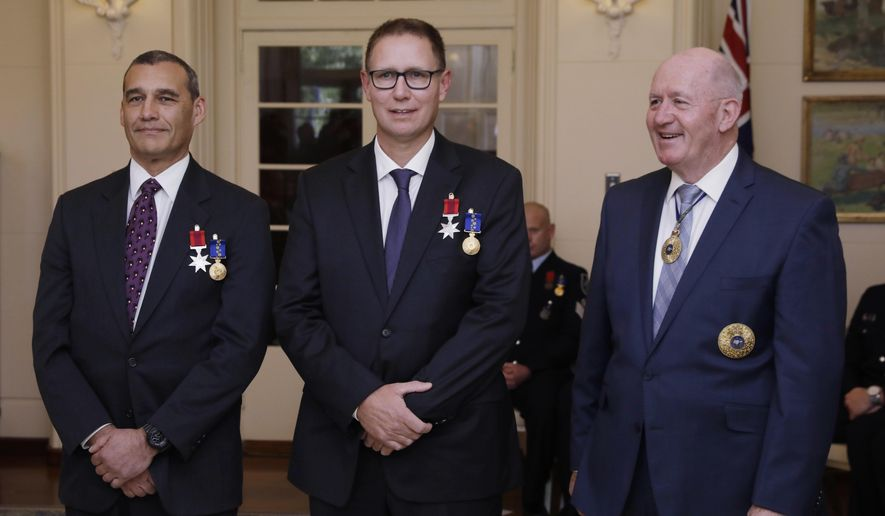 Australian members of the Thai cave rescue team, Craig Challen, left, and Dr. Richard Harris, center, stand with Australia's Governor-General Peter Cosgrove at a function at Government House in Canberra, Australia, Tuesday, July 24, 2018. Harris and his dive buddy Challen were awarded the Star of Courage, the second highest civilian bravery decoration in the Australian honors system after the Cross of Valor, Cosgrave said in a statement. (Sean Davey/AAP Image via AP)