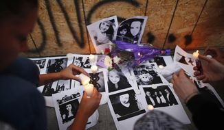 People light candles and leave photos of 18-year-old victim Reese Fallon at a memorial remembering the victims of Sunday's shooting in Toronto on Monday, July 23, 2018. A man whose family said he suffered from psychosis and depression fired a handgun into restaurants and cafes in a lively Toronto neighborhood, killing a 10-year-old girl and an 18-year-old woman and wounding over a dozen others in an attack that has shaken the confidence of many in the normally safe city. (Mark Blinch/The Canadian Press via AP)