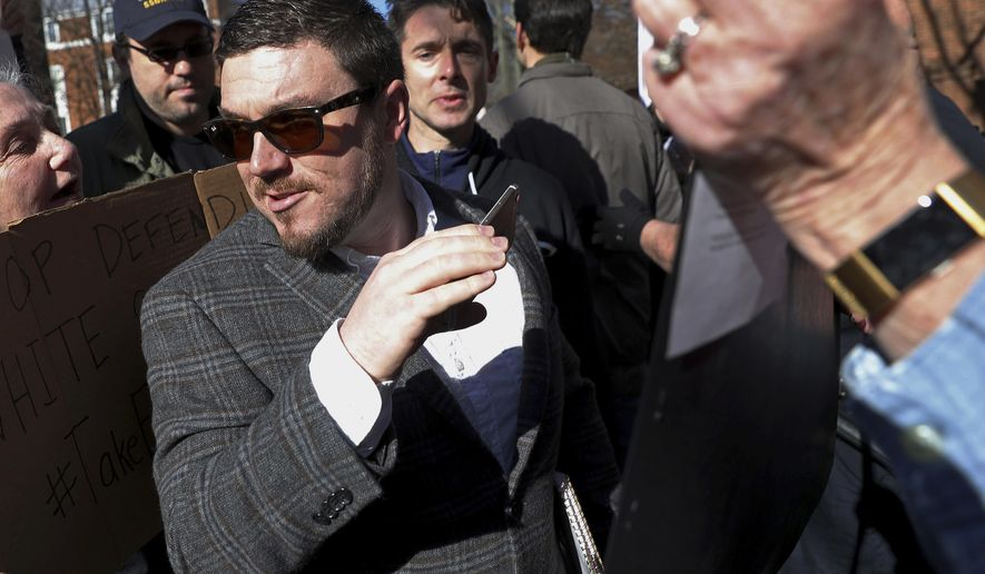 FILE - In this Feb. 27, 2018, file photo, Jason Kessler walks through a crowd of protesters in front of the Charlottesville Circuit Courthouse ahead of a decision regarding the covered Confederate statues, during a rally in Charlottesville, Va. Kessler, a white nationalist, is seeking a court order that would allow him to stage an event marking the anniversary of last year's rally in Charlottesville. U.S. District Judge Norman Moon scheduled a hearing Tuesday, July 24, on Kessler's request for a preliminary injunction that would compel the city of Charlottesville to issue him a rally permit for August. (Zack Wajsgras/The Daily Progress via AP, File)
