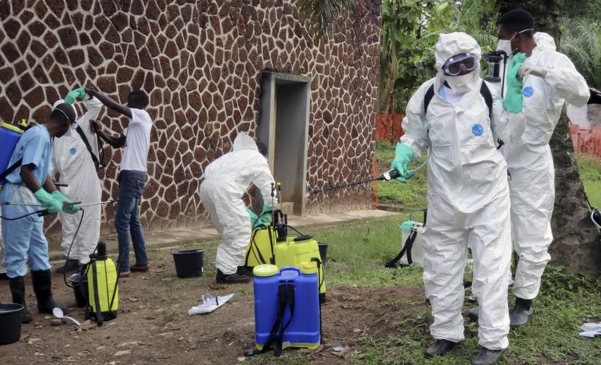 FILE - In this file photo taken Thursday, May 31, 2018, Congolese health officials prepare to disinfect people and buildings at the general referral hospital in Mbandaka, Congo.  Congo's Health Minister Oly Ilunga Kalenga on Tuesday July 24, 2018, declared the end of the country's latest deadly outbreak of the Ebola virus, after a 42-day observation period with no new confirmed cases recorded. (AP Photo/John Bompengo, FILE)