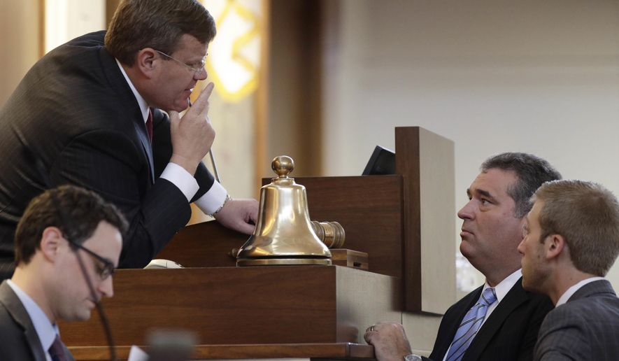North Carolina House Speaker Tim Moore, R-Cleveland, upper left, speaks with Rep. David Lewis, R-Harnett and aid Marl Coggins, right, during a special session at the General Assembly in Raleigh, N.C., Tuesday, July 24, 2018. The North Carolina legislature has called itself into an unscheduled session starting Tuesday because some Republican leaders fear a Democratic-controlled panel could add ballot wording for proposed constitutional amendments that dim their chance of passage in November. (AP Photo/Gerry Broome)
