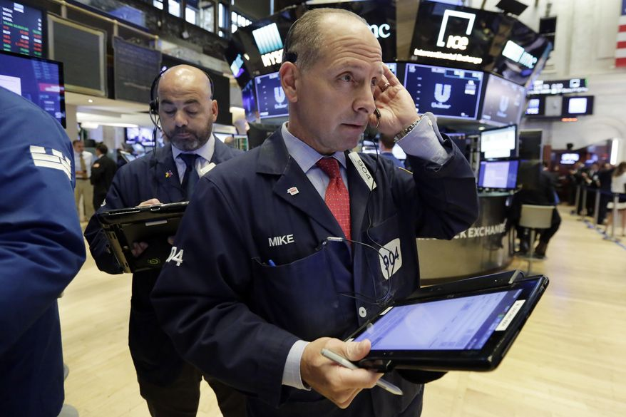 Traders Fred DeMarco, left, and Michael Urkonis work on the floor of the New York Stock Exchange, Tuesday, July 24, 2018. Stocks are opening broadly higher on Wall Street as investors were pleased to see strong earnings reports from a number of U.S. companies. (AP Photo/Richard Drew)