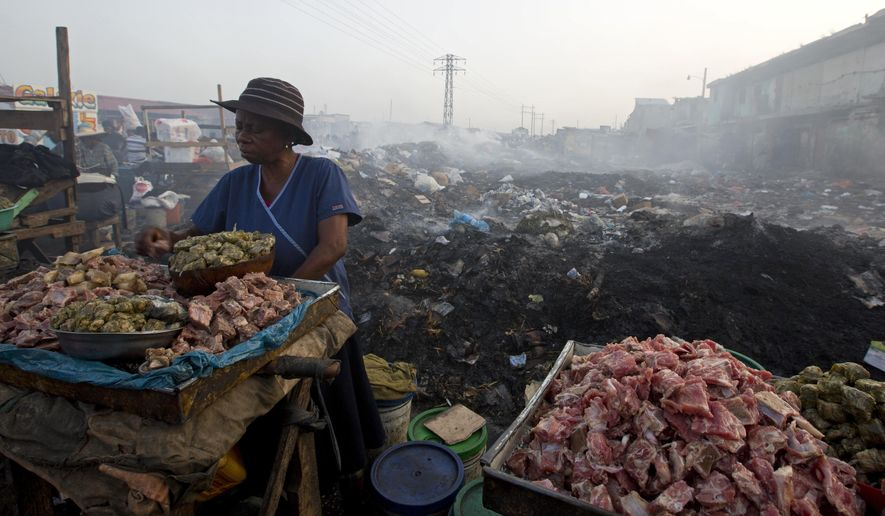In this July 18, 2018 photo, a vendor sells meat at the Croix des Bossalles market in Port-au-Prince, Haiti. Chicken is a staple of the Haitian diet but its price has doubled over the past four years. (AP Photo/Dieu Nalio Chery)