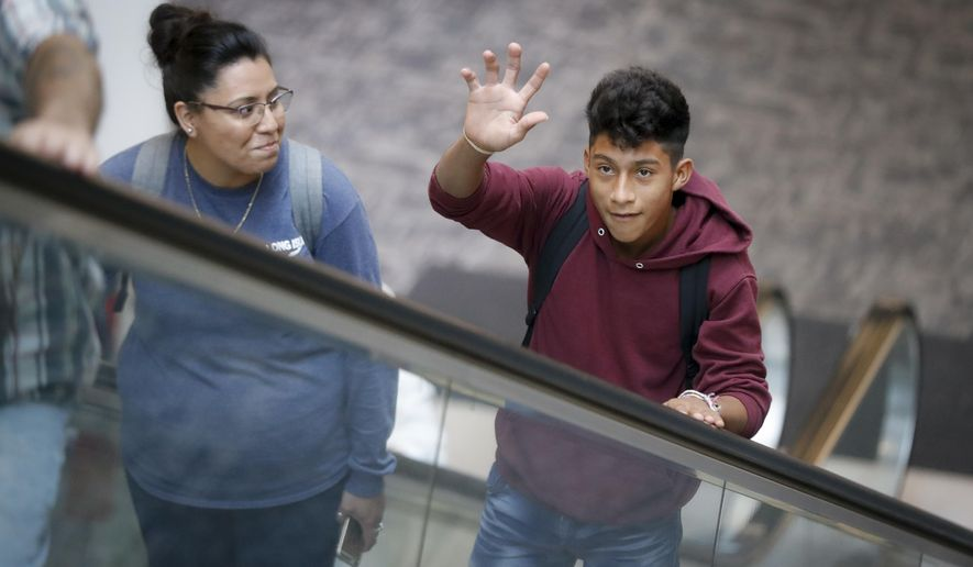 "Samuel Cazun, of Guatemala, right, waves to his family at Cincinnati/Northern Kentucky International Airport before reuniting with his father Edvin after being separated about a month ago at the southern border after they crossed the Rio Grande into the United States, Monday, July 23, 2018, in Hebron, Ky. Edvin said they were separated at the ""detention"" and he spent 15 days without knowing anything about his son. (AP Photo/John Minchillo)"