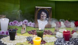 FILE - In this June 15, 2016, file photo, a picture of Berta Caceres sits on an altar in her honor during a demonstration outside Honduras' embassy in Mexico City. Activists demanded justice after the murder of Caceres, a Lenca Indian activist who won the 2015 Goldman Environmental Prize for her role in fighting a dam project. She was shot dead by two men on March 3. Global Witness said Tuesday, July 24, 2018 that at least 207 people who were protecting land and resources from business interests were slain last year. (AP Photo/Eduardo Verdugo)