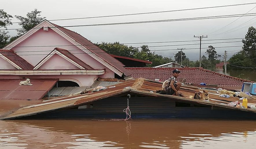 A villager takes refuge on a rooftop above flood waters from a collapsed dam in the Attapeu district of southeastern Laos, Tuesday, July 24, 2018. The official Lao news agency KPL reported Tuesday that the Xepian-Xe Nam Noy hydropower dam in Attapeu province collapsed Monday evening, releasing large amounts of water that swept away houses and made more than 6,600 people homeless. (Attapeu Today via AP)