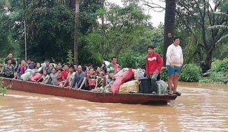 In this Tuesday, July 24, 2018, image from video, people on a boat are evacuated in the floodwaters from a collapsed dam in southeastern Laos. Rescue efforts are ongoing in villages flooded after part of a newly built hydroelectric dam was breached in southeastern Laos. (Attapeu TV via AP)