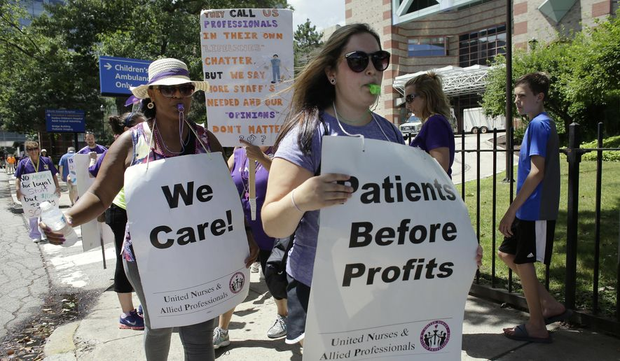 Nurses, medical workers, and family members picket, Tuesday, July 24, 2018, in front of Hasbro Children's Hospital, in Providence, R.I. Nurses at two Rhode Island hospitals, Hasbro Children's Hospital and Rhode Island Hospital, which are next door to one another, went on strike Monday, July 23, 2018, after negotiators couldn't agree on contract terms during a meeting requested by a federal mediator. (AP Photo/Steven Senne)