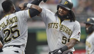 Pittsburgh Pirates' Josh Bell, right, is congratulated by Gregory Polanco after Bell hit a two-run home run in the fifth inning of a baseball game, Tuesday, July 24, 2018, in Cleveland. (AP Photo/Tony Dejak)