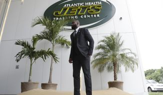 Former New York Jets cornerback Darrelle Revis stands in front of a makeshift island at the main entrance to the team's training facility after a news conference officially announcing his retirement Tuesday, July 24, 2018, in Florham Park, N.J. Revis leaves behind an 11-season career that included four All-Pro selections and a Super Bowl win with the New England Patriots. (AP Photo/Julio Cortez)