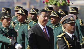 Chinese President Xi Jinping, center, inspects the honour guard during an official welcoming ceremony at the government's Union Buildings in Pretoria, South Africa, Tuesday, July 24, 2018. Jinping is in the country to attend the three-day BRICS Summit starting Wednesday in Johannesburg. (AP Photo/Themba Hadebe)