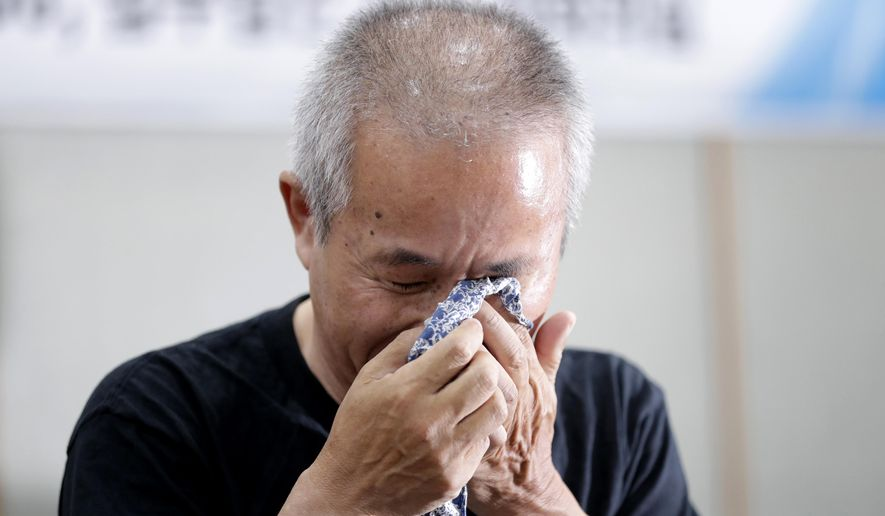 Hwang Sang-gi, father of former Samsung semiconductor factory worker Hwang Yu-mi who died from leukemia in 2007, wipes his tear during a signing ceremony in Seoul, South Korea, Tuesday, July 24, 2018. Samsung Electronics and a group representing ailing Samsung computer chip and display factory workers say they have agreed to end a years-long standoff over compensation for deaths and grave illnesses among Samsung workers. (AP Photo/Lee Jin-man)