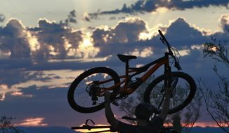 A man lifts his bike off his roof rack to beat the heat with an early start at dawn, Tuesday, July 24, 2018 in Phoenix. Much of Arizona and parts of California, Arizona and Utah are under an excessive heat watch during a week that forecasters say could prove to be the hottest of the year. (AP Photo/Matt York)