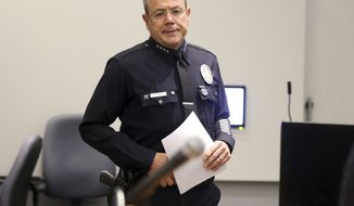 Los Angeles Police Chief Michel Moore approaches the podium at a news conference at police headquarters Tuesday, July 24, 2018, in Los Angeles, where he announced that a store worker killed in a gun battle before a suspect took hostages in a crowded supermarket was hit by a police officer's bullet. The employee, Melyda Corado, 27, was leaving the store Saturday, July 21, as the suspect, Gene Evin Atkins, 28, was going into the store after firing two rounds officers pursuing him, Moore told reporters. The two officers each fired back at Atkins and one of their rounds went through one of Corado's arms and into her body. (AP Photo/Reed Saxon)