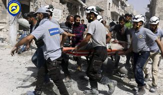 FILE - In this Wednesday, Sept. 21, 2016, file photo, provided by the Syrian Civil Defense White Helmets, rescue workers move a victim from site of airstrikes in the al-Sakhour neighborhood of the rebel-held part of eastern Aleppo, Syria. The call to get ready came at night. In the raging war zone of southwestern Syria, with enemy government forces on the march, the 98 White Helmets were told to bring spouses, children and but a few belongings to two collection points. Fabled rescuers themselves now in need of rescue, they embarked on a hair-raising journey through Israel, a supposed enemy, enroute to reluctant haven in Jordan, a country already burdened with multitudes of refugees. One woman gave birth along the way, many colleagues were left behind to a fate uncertain, and Syria called the multinational operation by several Western powers a crime. (Syrian Civil Defense White Helmets via AP, File)