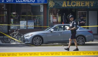 Police are investigate a car with a bullet hole within the scene of a shooting in east Toronto, on Monday, July 23, 2018. Police were trying Monday to determine what prompted a 29-year-old man to go on a shooting rampage in a popular Toronto neighborhood. (Christopher Katsarov/The Canadian Press via AP)