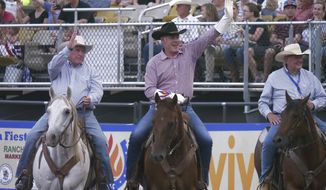Interior Secretary Ryan Zinke, center, rides around the arena and waves to the crowd after speaking at the Days of '47 Rodeo, on the Utah holiday Pioneer Day, Tuesday, July 24, 2018, in Salt lake City. It's one of several events on the Pioneer Day holiday that celebrates the arrival of Mormon pioneers in the Salt Lake Valley. (AP Photo/Rick Bowmer)