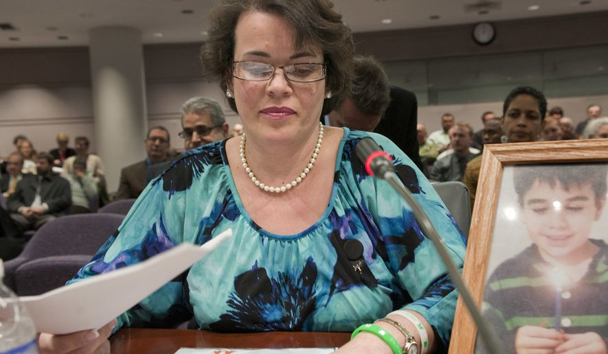 In this Jan. 28, 2013, file photo, Veronique Pozner places her hand next to artwork made by her son Noah's before testifying before a hearing of a legislative subcommittee reviewing gun laws at the Legislative Office Building in Hartford, Conn. Leonard Pozner and Veronique De La Rosa, the parents of Noah Pozner, wrote Facebook founder Mark Zuckerberg a letter published Wednesday, July 25, 2018,  in The Guardian asking him asking Facebook founder Mark Zuckerberg to remove hateful and harassing comments posted by conspiracy theorists who say the shooting never happened.  (AP Photo/Jessica Hill, File)