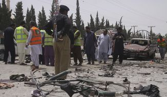 Pakistani security personnel visit the site of bombing in Quetta, Pakistan, Wednesday, July 25, 2018. A suicide bomber struck outside a crowded polling station in Pakistan's southwestern city of Quetta, killing many people as Pakistanis cast ballots Wednesday in a general election. (AP Photo/Arshad Butt)